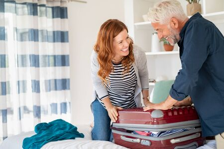 Mature smiling couple trying to close suitcase with too much clothes for vacation. Middle aged couple trying to close overstuffed suitcase for travel. Senior man and woman having fun while packing suitcase full with clothes for summer holiday, copy space.