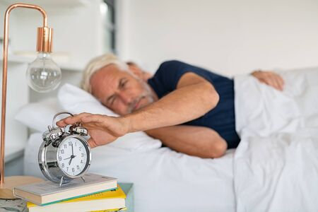 Old sleepy man lying on bed and stopping alarm clock with his wife in background. Senior man lying on side on bed turning off an alarm clock in the morning at 7am. Mature adult waking up in the morning. Banque d'images