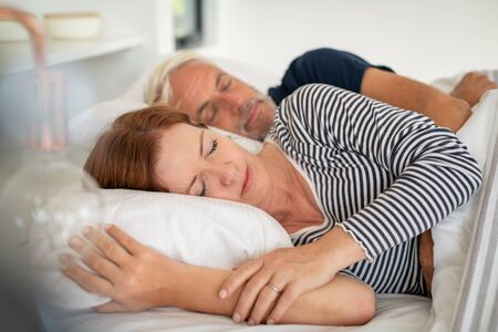 Mature relaxed woman dreaming and sleeping with her husband on bed at home. Senior man embracing beautiful asleep woman with eyes closed in the morning. Mature couple sleeping together in their bed.
