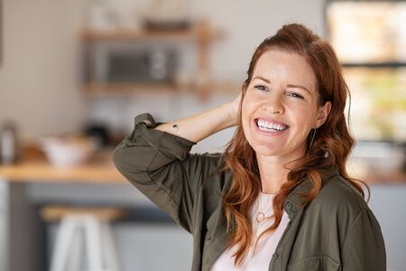 Portrait of beautiful mature woman at home. Successful middle aged woman smiling and looking away while touching hair. Mid redhead lady laughing and relaxing. Banque d'images