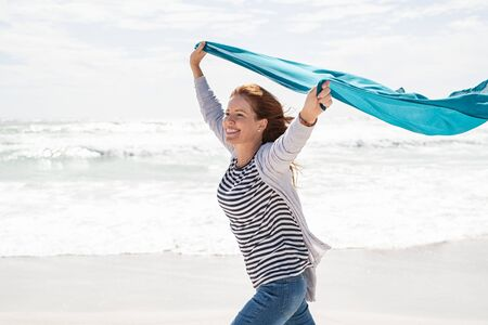 Happy smiling woman running with lightblue scarf enjoying at beach. Beautiful redhead woman holding blue fabric at wind in a summer vacation. Middle aged mature woman having fun at seashore with copy space: freedom and carefree concept.