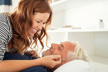 Middle aged lovely woman lying on happy senior man and caresses him. Handsome old man and attractive woman enjoying spending time together while lying in bed. Mature smiling couple in love at home, copy space. Banque d'images