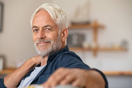 Portrait of a smiling mature man relaxing on couch with copy space. Confident senior man resting at home and looking at camera. Satisfied retired man with grey hair sitting on sofa at home. Banque d'images