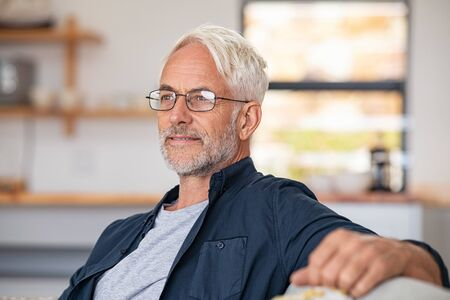 Retired mature man sitting on couch wearing spectacles and thinking. Smiling and cheerful old man planning the retirement. Thoughtful senior business man relaxing at home while looking away with copy space.