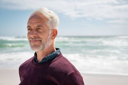Portrait of pensive senior man at beach during sunny day looking away. Proud and satisfied old man in casual enjoying summer holiday at beach. Mature retired man contemplating at sea: iImagination and future concept.