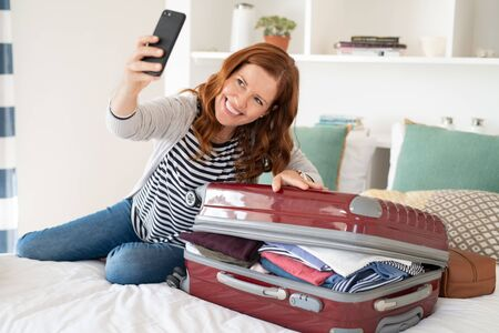 Beautiful mature woman taking selfie with overstuffed suitcase before leaving for a trip. Cheerful middle aged woman sitting on bed using smartphone taking picture with unpacked bag before vacation. Mid woman in video call at home preparing for travel.
