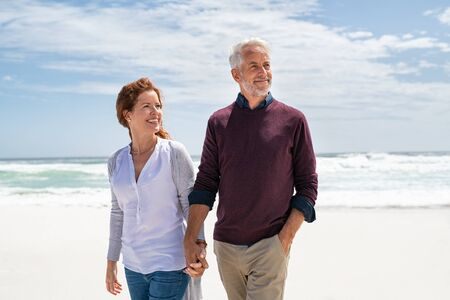 Happy senior couple holding hands at beach in a sunny autumn day. Loving mature couple enjoying their vacation at the sea shore with copy space. Smiling wife and happy old husband walking barefoot on the white sand.