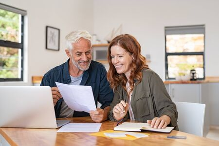 Mature smiling couple sitting and managing expenses at home. Happy senior man and mid woman paying bills and managing budget. Middle aged couple checking accountancy and bills while looking at receipt. Banque d'images