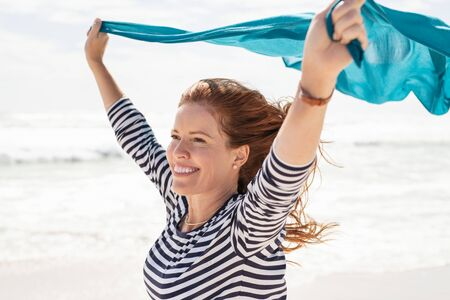Smiling mature woman holding blue scarf over head while walking at beach. Happy active and healthy woman enjoying summer vacation at sea. Middle aged lady in casual running at seashore with blue fabric.