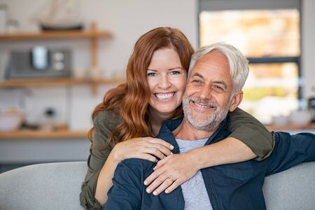 Smiling woman hugging her senior husband on couch from behind in the living room. Loving retired couple looking at camera and smiling at home. Portrait of smiling woman embracing mature man on sofa. Banque d'images