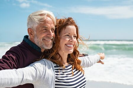 Romantic senior couple with outstretched arms enjoying vacation. Old husband embracing from behind beautiful wife during honeymoon at sea. Happy smiling mature couple carefee: future, imagination and conteplation concept. Banque d'images