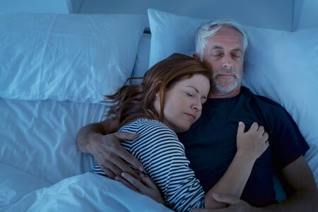 Senior man and woman sleeping and dreaming together in a deep sleep. Mature woman embracing and sleeps on her husband's chest while sleeping at night. Loving couple resting in their bed, copy space.