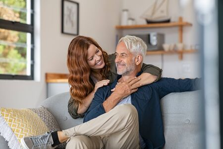 Smiling woman hugging her husband from behind in the living room. Loving mature couple sitting on couch and looking at each other. Mid adult beautiful woman embracing smiling senior at home. Banque d'images