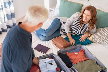 High angle view of mature man packing stuff into suitcase at home. Happy mature couple packing clothes into suitcase in bedroom. Top view of cheerful smiling wife lying on bed with husband arranging accessories in bag for travel. Banque d'images