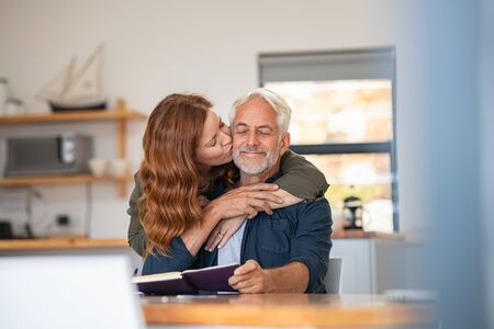 Happy loving woman kissing old man on cheek at home. Beautiful mature wife kissing her husband with beard and closed eyes. Senior couple in love. Banque d'images