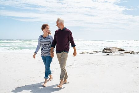 Senior couple walking and looking at each other at beach. Happy mature couple in love in a bright sunny day walking barefoot at sea shore. Loving retired man with beautiful casual woman relaxing at the ocean with copy space. Banque d'images