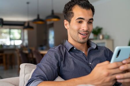 Happy smiling latin man with smartphone being surprised as reading message while sitting on sofa. Indian man sitting on couch looking at his mobile phone with a surprised expression. Hispanic guy with cellphone relaxing at home while receive great news from friend.