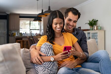 Mixed race young couple using mobile phone together sitting on sofa in the living room. Cute loving indian couple messaging on smartphone together at home. Happy man embracing smiling woman from behind while watching video online in a smart phone.