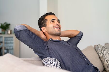 Young indian man at home relaxing and thinking with hands behind head. Middle eastern pensive guy resting at home. Latin thoughtful man sitting on couch while looking up.