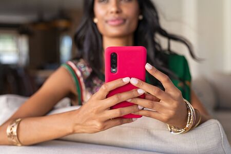 Close up hands of young indian woman in traditional clothing holding smartphone. Hindu girl in ethnic wear, sari, with bracelets sitting on couch and using cellphone. Detail of indian girl hands typing message on mobile phone at home. Banque d'images