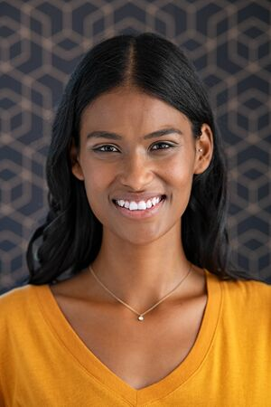 Portrait of young indian woman smiling. Close up face of happy successful mixed race woman looking at camera. Beautiful girl with long black hair standing against pattern background.