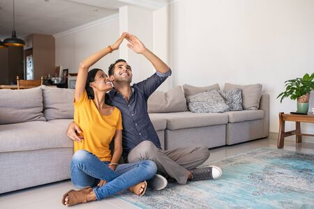 Handsome young man with beautiful indian woman dreaming a new home. Happy young married couple moves to new apartment with copy space. Happy middle eastern couple making roof with hands symbol of new home and insurance protection plan.