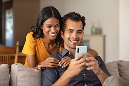 Indian couple using smartphone together in living room at home. Handsome latin man sitting on couch showing woman a video while she is standing behind. Beautiful midlle eastern girl embracing from behind her boyfriend while doing video call on mobile phone, copy space.