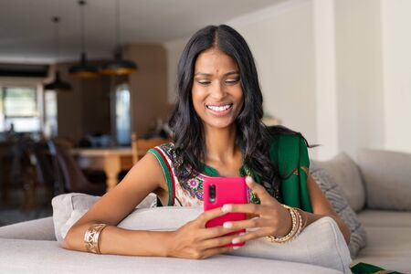 Smiling indian girl in traditional sari using smartphone at home. Young woman in ethnic wear sitting on couch and sending phone message with smartphone. Cheerful beautiful hindu woman with bindi using app on mobile phone.