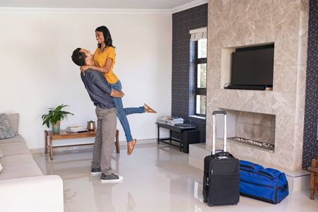 Romantic young indian man lifting beautiful woman near luggage in new house for holiday. Joyful middle eastern couple moving into their new home. Husband carrying his wife in modern apartment rented for vacation.