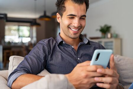 Cheerful businessman using smartphone while sitting on sofa at home. Handsome young indian man sitting on couch reading messages on mobile phone. Hispanic guy working from home with cellphone. Banque d'images