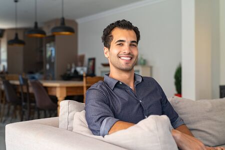 Portrait of happy young middle eastern man sitting on sofa at home. Handsome latin man in casual relaxing on couch in bright living room. Cheerful smiling mixed race guy looking at camera. Banque d'images