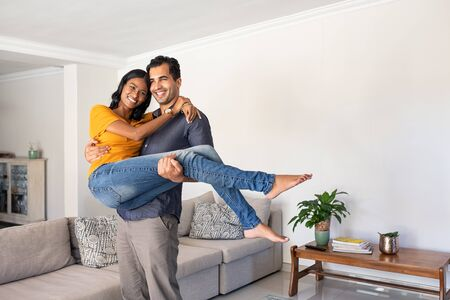 Romantic young middle eastern man lifting woman holding in hands. Joyful couple moving into their new home with husband carrying his wife. Man carrying indian woman in his arms moving in booking house for vacation.