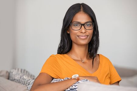 Portrait of middle eastern woman wearing eyeglasses and relaxing on couch at home. Successful indian girl with spectacles thinking while sitting on couch and looking at camera. Satisfied young woman stay at home with copy space. Banque d'images