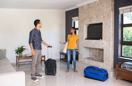 Young indian couple feeling excited on moving in new house. Young man and beautiful woman arrive in the holiday house booked online. Middle eastern couple with suit case in a conversation while checking their place for vacation.  Banque d'images