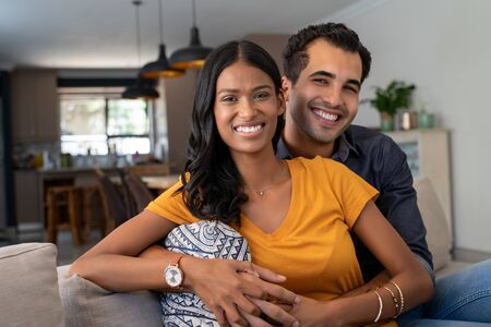 Portrait of happy young indian couple relaxing together on couch. Middle eastern couple cuddling on couch at home in the living room while looking at camera. Portrait of lovely man embracing from behind his beautiful girlfriend sitting in sofa. Banque d'images