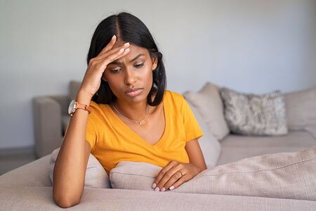 Sad depressed indian woman at home sitting on couch, looking down and touching her forehead. Stressed young woman alone at home with copy space. Frustrated and unhappy middle eastern girl with terrible migraine or headache.
