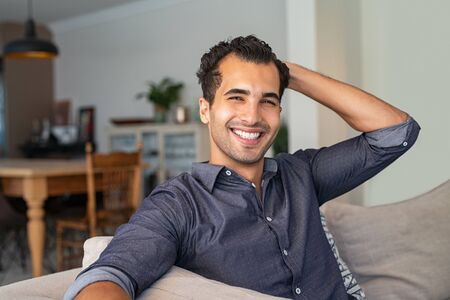 Happy successful young businessman relaxing on a comfortable sofa. Portrait of smiling indian man looking at camera sitting on couch while run his hand through his hair. Stylish middle eastern guy relaxing at home.
