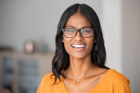 Porträt der jungen indischen Frau mit Brille zu Hause. Erfolgreiche Mischrassefrau mit Brille und Blick in die Kamera. Fröhliches schönes Mädchenlächeln.