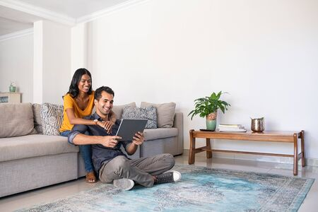 Young middle eastern couple using digital tablet at home while sitting on couch and floor. Indian woman embracing from behind her boyfriend while watching video on digital tablet at home. Happy smiling couple in video call conference, copy space.
