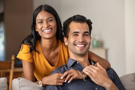 Smiling indian woman hugging her husband on the couch from behind at home. Loving middle eastern couple looking at camera with big grin in the living room. Portrait of laughing girl embracing handsome latin man on sofa.