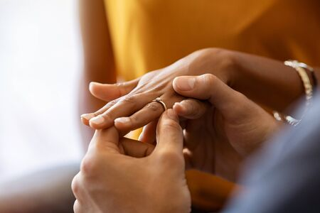 Close up of man putting beautiful engagement ring on his girlfriend hand. Man is making marriage proposal with golden ring with diamond to his woman. Close up hands of indian guy giving an engagement ring: do you want to marry me?
