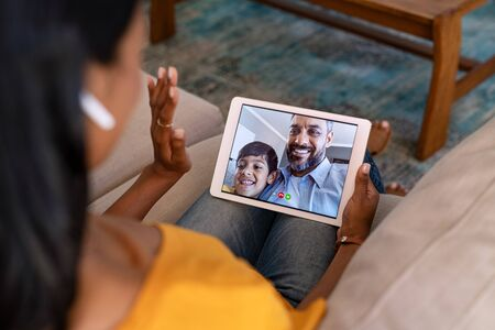 Rear view of indian mother doing a video call with her husband and son. Young woman relaxing at home while on conversation with middle eastern man and smiling boy on digital tablet. Happy latin family in video conference through videochat.