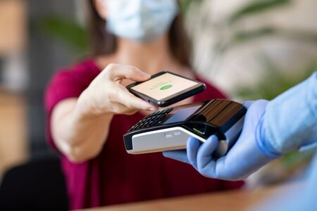 Close up hand of customer paying with smartphone. Cashier hand holding credit card reader machine and wearing protective disposable gloves at bar counter, while client holding phone for NFC payment. Woman wearing face mask while paying bill with mobile phone during Covid-19 pandemic. 스톡 콘텐츠