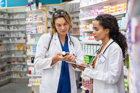 Two multiethnic pharmacists checking inventory at hospital pharmacy. Medical staff working in drugstore. Mature woman pharmacist with african colleague holding cough syrup and medicines. Foto de archivo