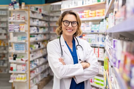 Portrait of mature woman pharmacist at pharmacy wearing labcoat with stethoscope. Happy smiling doctor standing in modern pharmacy drugstore. Friendly young pharmacist owner standing in shop and looking at camera. Foto de archivo