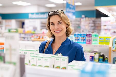 Portrait of smiling woman choosing dietary supplement at pharmacy in shopping mall. Happy mature woman customer buying lotion in skincare section of chemist's. Woman checking medicine and drugs in shelf at drugstore while looking at camera.