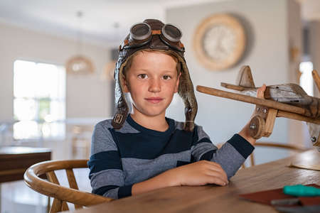 Portrait of little boy wearing pilot helmet playing with wooden airplane at home. School kid playing with wooden plane while looking at camera. Cute child holding wooden handmade airplane model with aviator helmet at home.