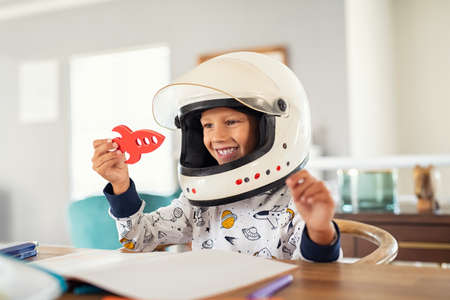 Little boy wearing an astronaut helmet costume and playing with a spaceship while doing homework. Little boy dreams of going into space while playing with red rocket at home. Small kid in astronaut pajamas with toy rocket playing and dreaming of becoming a spacemen.