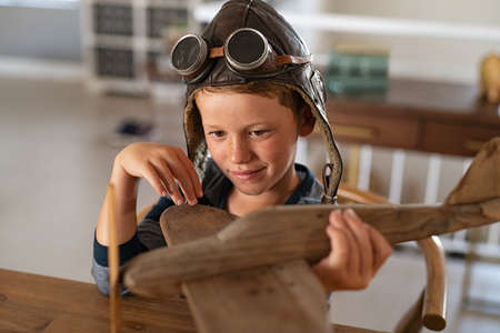 Boy wearing pilot helmet playing with vintage wooden airplane at home. Happy child playing with wooden flight simulator. Little boy holding handmade plane with pilot cap and goggles at home. 版權商用圖片