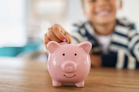 Close up of little boy saving coin into piggy bank at home. Closeup of child hand putting penny coin in piggy bank on table. Kid saving money by adding coin in pig shaped bank. Standard-Bild